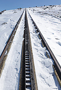 The Cog railroad tracks on the summit of Mount Washington in the White Mountains, New Hampshire during the winter months. Mount Washington, at 6,288 feet, is the tallest mountain in the northeastern United States.