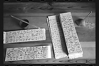 Wumu Village, Yulong County, Yunnan Province, China - Dongba priest He Jixian of the Naxi ethnic group writes scripture, June 2019.