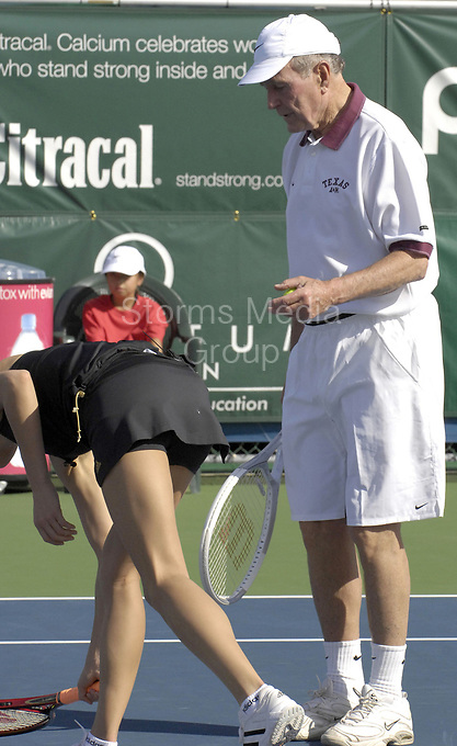DELRAY BEACH, FL - NOVEMBER 5, 2006: Tennis Hottie Anna Kournikova hits Former President George W. Bush in the bum with a blistering serve at the Delray Beach Tennis Center on November 5, 2006 in Delray Beach, Florida<br /> <br /> People:  Former President Bush; Anna Kournikova