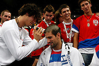 Novak Djokovic (center)gets a celebratory haircut on the court right after the Serbian national tennis team won the Davis Cup finals against France in Belgrade Arena, Belgrade, Serbia, Sunday, December. 5, 2010. (credit & photo: Pedja Milosavljevic/SIPA PRESS)