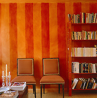 A pair of dining chairs are upholstered in striped fabric which mirrors the red and orange hand-painted striped walls in this sitting room