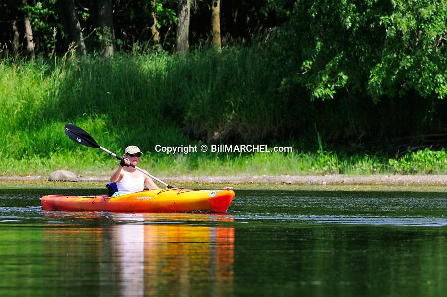 00702-001.04 Kayaking: Woman is kayaking on river.   Mississippi, lake, water.