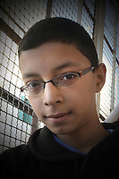 13-years-old Waleed Abu Aishe in the city of Hebron. About 800 Jewish settlers live in the heart of the city, protected by around 4,000 soldiers, amid a Palestinian population of 170,000. In 1997 the city was divided into H1, administered by the Palestinian Authority, and H2, a much smaller area around the old market, under the control of the Israeli military. H2 is now a near-ghost town: shuttered shops, empty houses, deserted streets, packs of wild dogs, and armed soldiers on most street corners. Here, the remaining Palestinian families endure an uneasy co-existence with their settler neighbours. In Tel Rumeida, Waleed's neighbourhood, almost all the Palestinian residents have left. Only the Abu Aishes and another family remain on his street. Following violent attacks, stone-throwing, smashed windows and repeated harassment from settlers, the Abu Aishes erected a steel mesh cage and video cameras over the front of the three-storey house where the family has lived for 55 years. When not at school, Waleed spends almost all his time inside this cage.