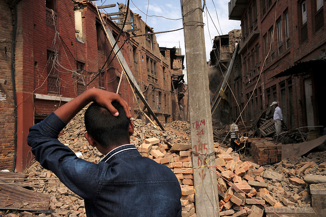 A resident pauses to look at an earthquake devastated neighborhood in Bhaktapur, Kathmandu Valley, Nepal in June 2015. Painstaking cleanup was underway with many residents are using their own hands and simple tools to stabilize their homes before the arrival of heavy monsoon rains.