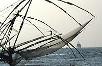 INDIA Kerala, Fort Cochin, chinese fishing net at port entry, behind indian navy ship / INDIEN Kerala, Cochin Kochi, lokale Küstenfischer leeren die chinesischen stationären Senknetze an Hafeneinfahrt , indisches Marine Schiff