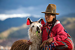 A Peruvian woman dressed in traditional clothing holds her pet llama in Cuzco, Peru.