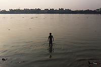 A man stands in the Ganges River at sunset near the Howrah bridge in Kolkata. Upon entering the city, the river is saturated with a mix of domestic and industrial waste that has accumulated as it has passed through numerous states in northern India, making it one of the most polluted rivers in the world. India. November, 2013