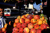 San Jose, Costa Rica. Street vendor selling large plums and other fruit from a stall.