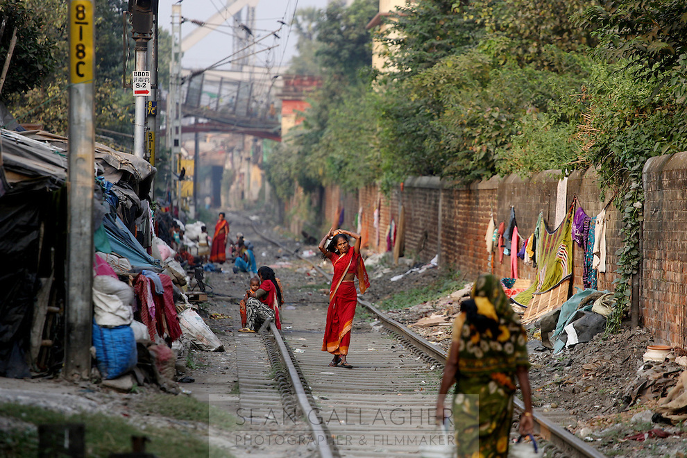 A woman walks along train tracks near a slum community in central Kolkata. It is estimated that over 3 million people live in the slums across the city. India. November, 2013