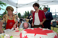 July 1 2002, Montreal, Quebec, Canada<br /> <br /> Lucienne Robillard, President Treasury Board of canada (L), get help from<br /> Justin Trudeau, Former Canada Prime Minister Pierrre E TRudeau's son (R) to cut a giant cake distributed to people attending the Canada day celebrations,  July 1st 2001, in the Old-Port of Montreal. <br /> <br /> Mandatory Credit: Photo by Pierre Roussel - Agence Quebec Presse