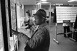 Unemployment Job Centre Labour Exchange South London. 1970s UK. On the dole black British African man, his partner behind him is also looking for work, multi ethnic Britain 1976  England.