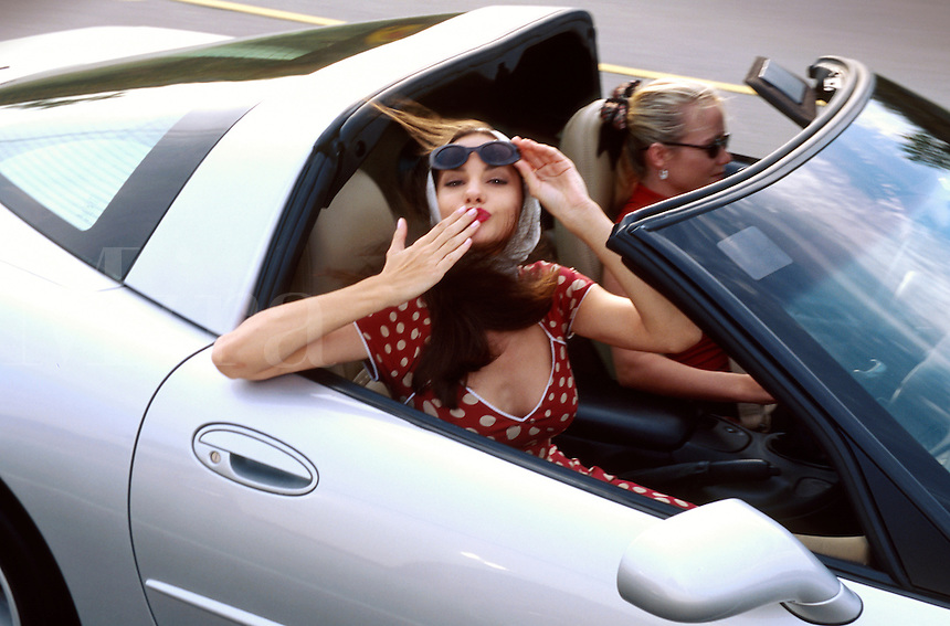 A smiling young woman blows a kiss as she rides with a friend in a silver Corvette convertible.