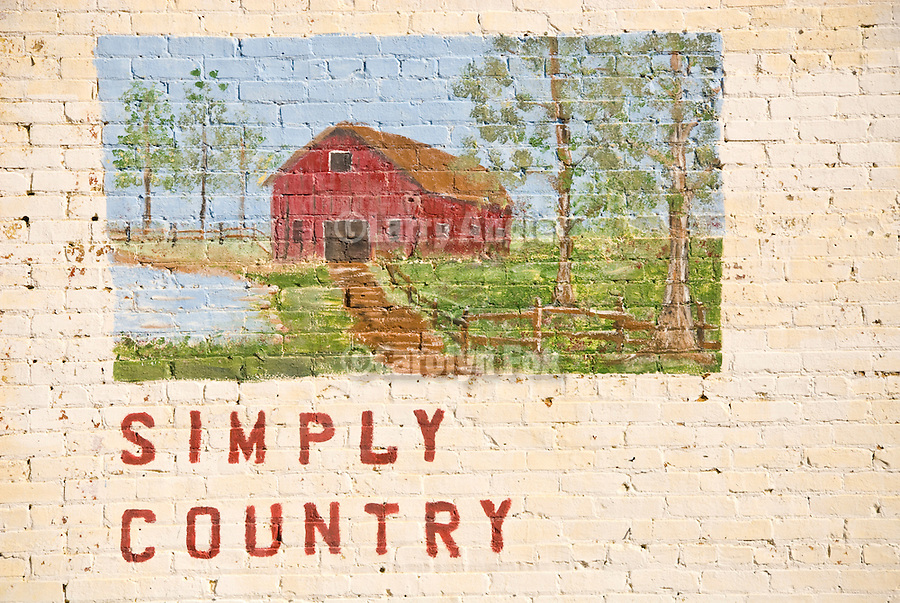 """Painting of a red barn on a brick wall inscribed """"Simply Country"""", Preston, Georgia."""