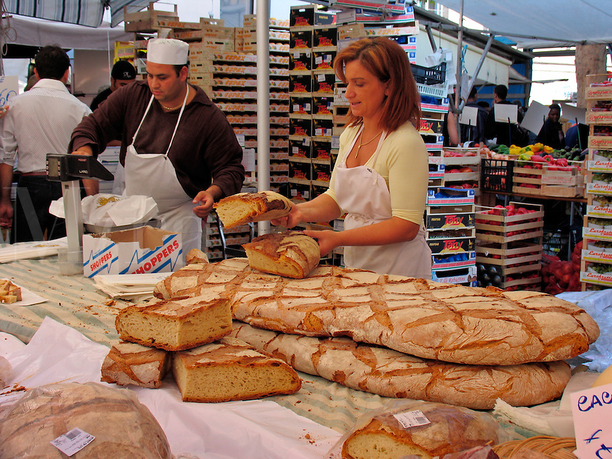 Woman slicing giant loaf of bread at booth at outdoor street market, Viale d Papiniano, Milan, Ital
