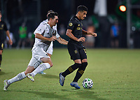 LAKE BUENA VISTA, FL - JULY 18: Mohamed El-Munir #13 of LAFC dribbles away from the pressure by Sacha Klestan #16 of LA Galaxy during a game between Los Angeles Galaxy and Los Angeles FC at ESPN Wide World of Sports on July 18, 2020 in Lake Buena Vista, Florida.