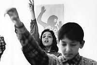 Hungary. Baranya County. Pécs. Gandhi High School.  German class. A girl and a boy with arms and hands raised signal that they know the answer. The purpose of the middle school / high school is to provide a school-leaving exam (A-level), also to improve the prospects of Romani children in Hungary and to help preserving the Romani culture. The Romani people, also known as the Roma, are an Indo-Aryan people group, traditionally nomadic itinerants living mostly in Europe. The Romani people are widely known in English by the exonym Gypsies (or Gipsies), which is considered by many Romani people to be pejorative due to its connotations of illegality and irregularity as well as its historical use as a racial slur. In many other languages, they are called Roms (Rroms), Tziganes,Tsiganes, Gitans, Bohémiens, Manouches, Romanichels, gitano, zingaro and cigano. The Gandhi High School in Pécs, was founded with donations given by several individuals from the private sector mostly those of Romani origin Romani and with further donations from other organizations. In 1992, the Gandhi High School became  the first Romani high school, that has been actively operating since 1994. It was named after the Indian Mahatma Gandhi, to emphasize the Indian origin of all Romani groups. The school consists of 6 classrooms where about 250 male and female pupils study, mostly between the ages of 14 to 18. The first group of students beginning in 1994 took their school-leaving exam (A-level) in 2000 and out of 18 pupils, 16 have applied to universities, while 7 out of the 18 students gained entry to their desired universities. Pécs is the fifth largest city of Hungary. It is the administrative and economic centre of Baranya County.11.05.95  © 1995 Didier Ruef