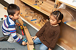 education preschool 3 year olds boy and girl playing together with wooden blocks and train set