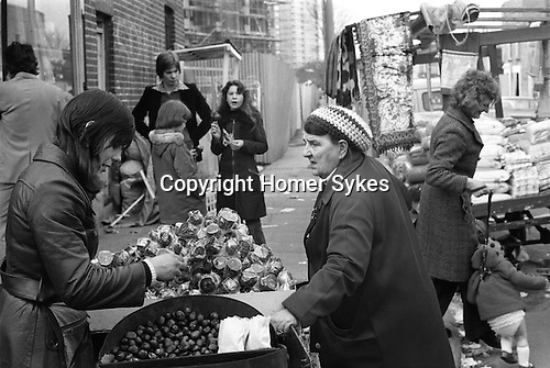 Tower Hamlets, London. 1975<br /> A market trader in Roman Road, sells hot roasted chestnuts and toffee apples with a hard brittle toffee exterior. They are protected by heavy duty clear cellophane wrapping.