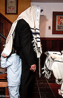 """Father of new born daughter conducts her naming ceremony (called """"brit bat"""") in private synagogue. Young son plays hide and seek behind tallis."""