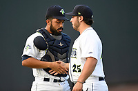 Catcher Carlos Sanchez (7) of the Columbia Fireflies shakes hands with catcher Scott Manea (25) after warm ups before a game against the Charleston RiverDogs on Wednesday, August 29, 2018, at Spirit Communications Park in Columbia, South Carolina. Charleston won, 6-1. (Tom Priddy/Four Seam Images)