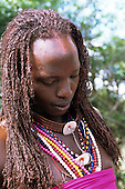 Lolgorian, Kenya. Siria Maasai Manyatta; Olelekule, moran, red ochre coloured braided hair, shell decoration.