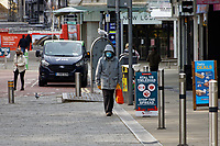 Pictured: A man with a face mask walks through Whitewalls. Friday 19 March 2021<br /> Re: City centre of Swansea, Wales, UK.