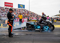 Aug 31, 2019; Clermont, IN, USA; NHRA top fuel driver Mike Salinas (left) watches as daughter Jianna Salinas races her pro stock motorcycle during qualifying for the US Nationals at Lucas Oil Raceway. Mandatory Credit: Mark J. Rebilas-USA TODAY Sports