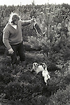 """Suffolk, man out rabbit shooting with two rough hair Jack Russell dogs. He told me he normally gets about eight rabbits in an hour or so, and sells them to his local skin merchant for eight shillings each. """"Its a good living."""" he said.1974 Suffolk East Angelia. UK. The UK went decimal in 1971, but he was still talking in pounds, shillings and pence!"""