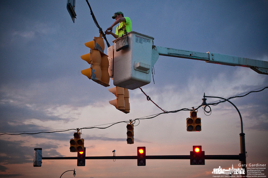 Construction crew electricians remove old traffic signals and turn on a set of new signals at in intersection in Westerville, OH.