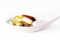 Close up of a spoon full of vitamins, supplements and herbs.