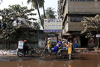 Pedestrians, bikes and motorbikes mix on a flooded street in Kolkata.<br />