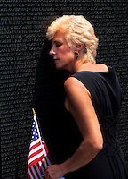 Woman sad and crying at loss of loved one at the Vietnam Monument in Washington DC USA.
