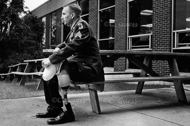 Army Sgt. Raymond Hubbard rests himself on a picnic bench behind Martin Luther High School after a John McCain presidential rally in Greendale, Wis. on Thursday, May 29, 2008.