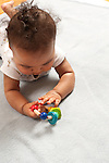 7 month old baby boy closeup on stomach interested in toy he holds transferring hand to hand