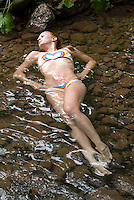 Young woman wearing bikini laying down in stream