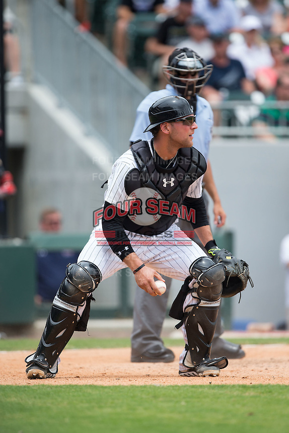 Charlotte Knights catcher Kevan Smith (32) picks up the baseball during the game against the Gwinnett Braves at BB&T BallPark on July 3, 2015 in Charlotte, North Carolina.  The Braves defeated the Knights 11-4 in game one of a day-night double header.  (Brian Westerholt/Four Seam Images)
