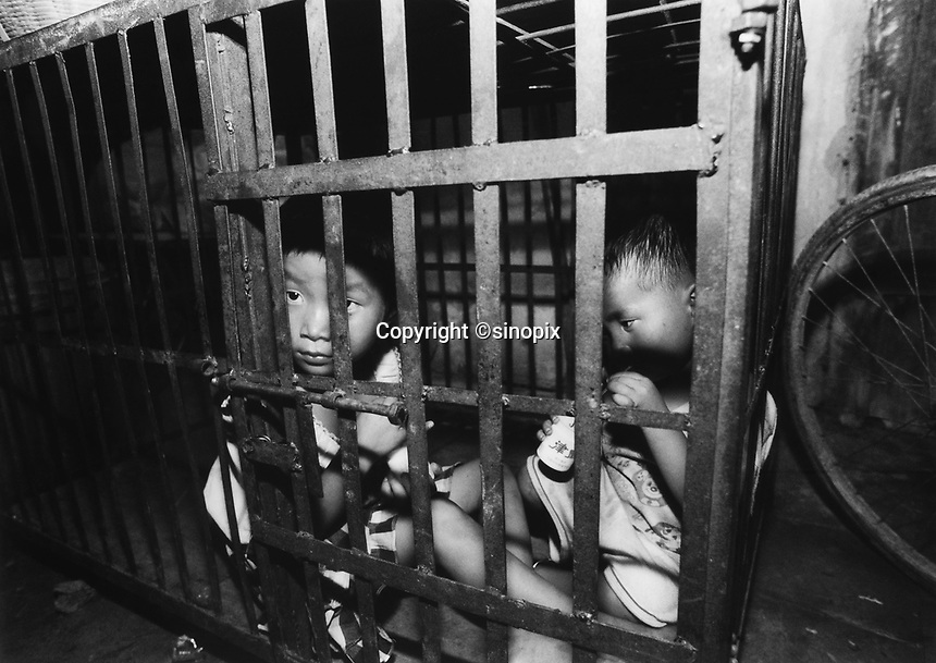 Children, aged 3 and 5, are kept in a cage in a village house belonging to their uncle. The children's parents are both in prison and the uncle is too poor to afford child care for the children.<br /><br />photo by Richard Jones / Sinopix