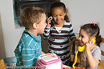 preschool 3-4 year olds pretend play boy and two girls playing with telephones and talking horizontal
