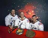 """The original Apollo 13 prime crew. From left to right are: Commander, James A. Lovell, Command Module pilot, Thomas K. Mattingly and Lunar Module pilot, Fred W. Haise. On the table in front of them are from left to right, a model of a sextant, the Apollo 13 insignia, and a model of an astrolabe. The sextant and astrolabe are two ancient forms of navigation. Command Module pilot Thomas """"Ken"""" Mattingly was exposed to German measles prior to his mission and was replaced by his backup, Command Module pilot, John L.""""Jack"""" Swigert Jr."""