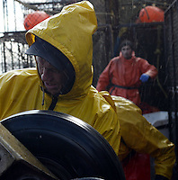 10/20/03 crab NWS::  Crewmen Lyndon Yockey of the F/V Exito mans the king coiler while water and jellyfish spray off the line into his face.  The 2003 Bristol Bay red king crab season lasted 5 days and 2 hours and was plagued with gale force winds of 35 knots or higher almost everyday causing 10 to 15 feet waves.
