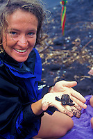 Woman holding baby hawksbill turtle hatchling