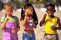 Mixed ethnic children playing on beach blowing bubbles having fun togethe