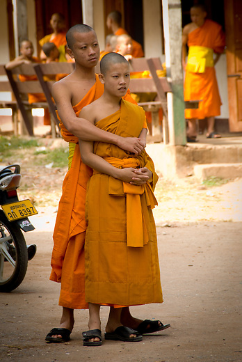 Young Buddhist monks in a friendly embrace. It is not uncommon to see this sort of affection amongst novice monks.  While they live a minimalist, sedentary life in the monastery, they welcome many of the 21st century conveniences like cell phones and internet.