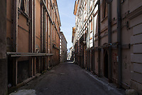 Inside the Red Zone delimiting the medieval center of L'Aquila. Thousands of historic buildings are kept standing by safety harnesses and shoring shells, abandoned streets and alleys are immersed in a surreal silence, broken only by sporadic groups of workers committed to securing and reconstructing. L'Aquila, Italy. Apr. 10, 2015