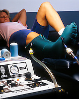 Female athlete with ankle injury in a Jobst cryo temp machine which applies both heat or cold and pressue to help heal sports injuries.