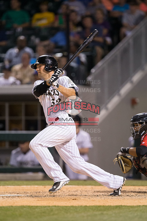 Kevan Smith (32) of the Charlotte Knights follows through on his swing against the Indianapolis Indians at BB&T BallPark on June 20, 2015 in Charlotte, North Carolina.  The Knights defeated the Indians 6-5 in 12 innings.  (Brian Westerholt/Four Seam Images)