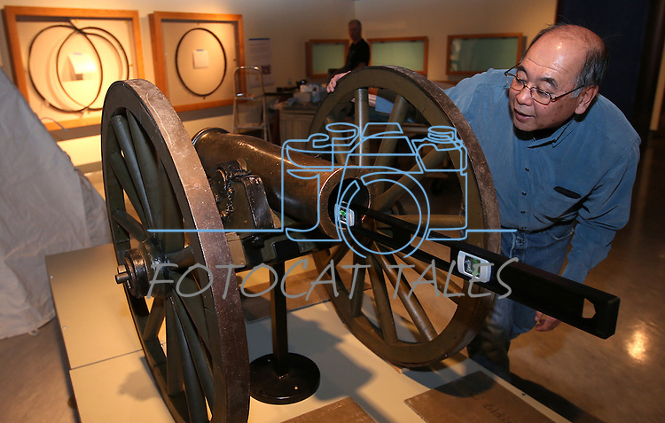 """Nevada State Museum Archaeologist Gene Hattori checks a level while setting up the Fremont Cannon as part of the """"Finding Fremont: Pathfinder of the West"""" exhibit at the museum in Carson City, Nev., on Monday, Jan. 27, 2014. (Las Vegas Review-Journal/Cathleen Allison)"""