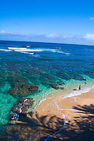 Surfer enters crystal clear waters of Hideaways Beach, a snorkeling heaven in Princeville, North Shore of Kauai