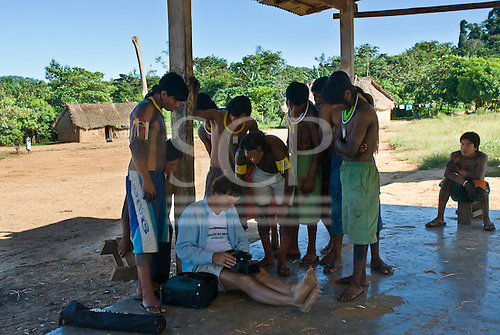 Pará State, Brazil. Aldeia Pukararankre (Kayapo). Patrick Cunningham showing pictures to a group of people on the camera.