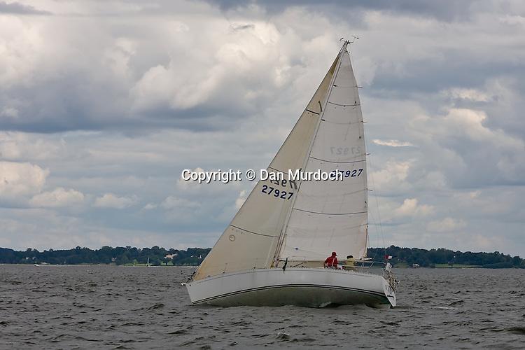 racing sailboat on port tack under a cloudy sky